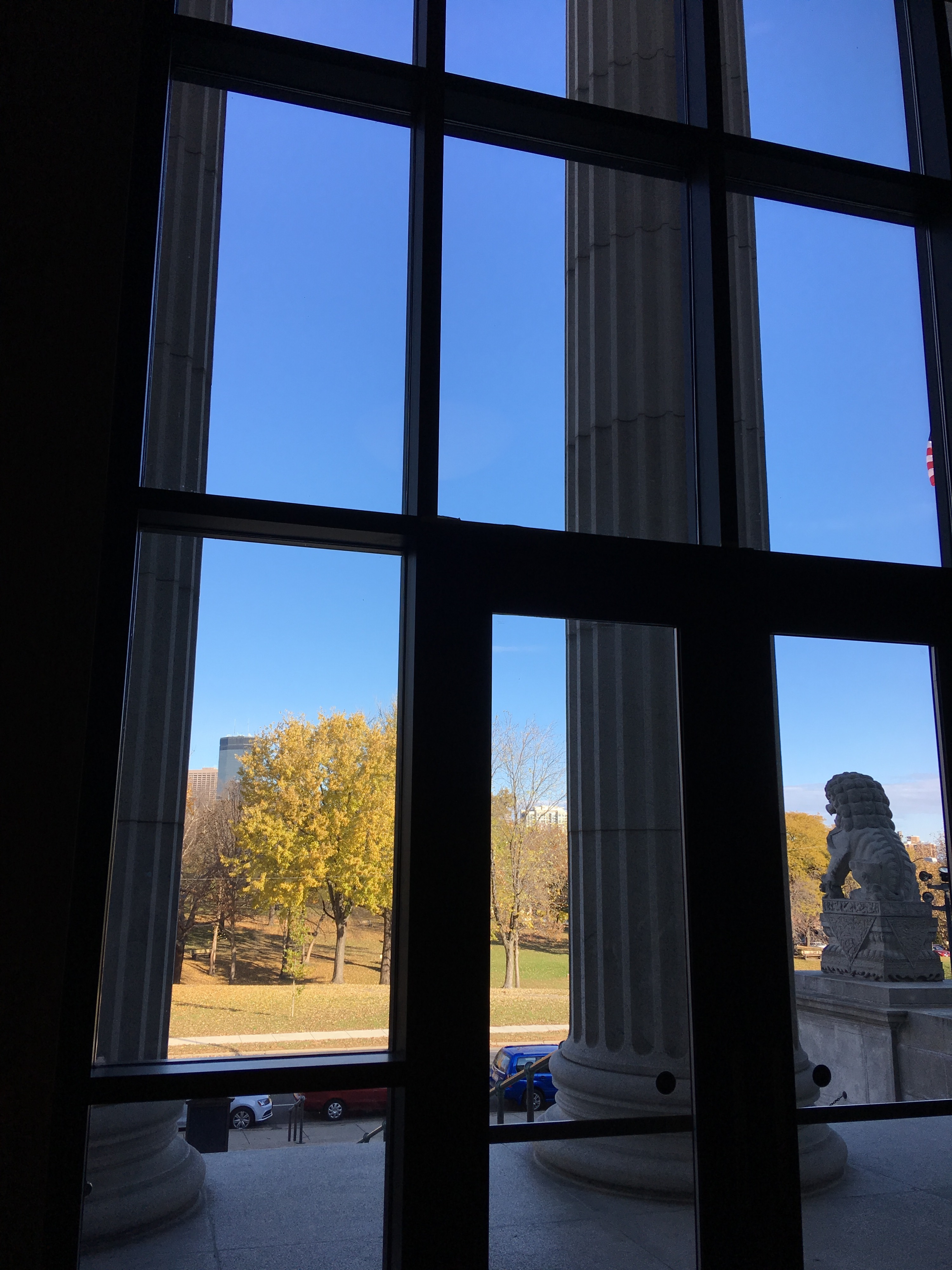 View out the front doors showing a pillar and a stone lion, the Minneapolis skyline partly hidden by autumn trees in the park across the street, all under a high, clear blue sky