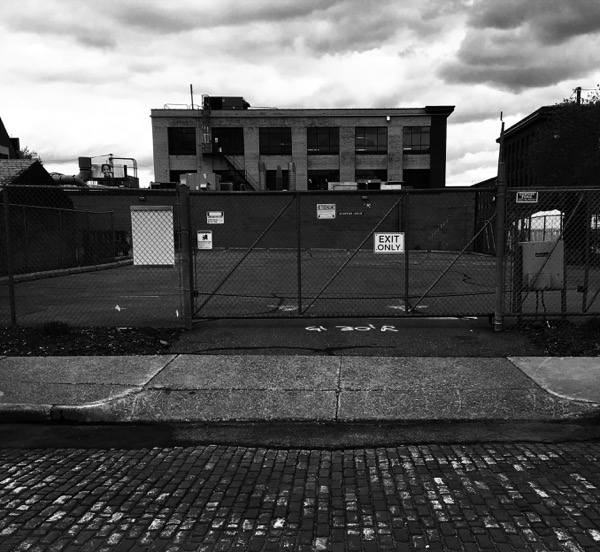 brick roadbed; closed fence gate with exit only sign; empty lot; warehouse; cloudy sky