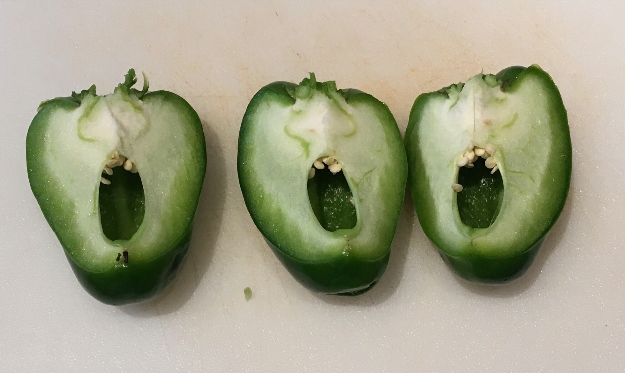 A green bell pepper cut in thirds from north to south pole. The gaps and the seeds make it look like three singing mouths