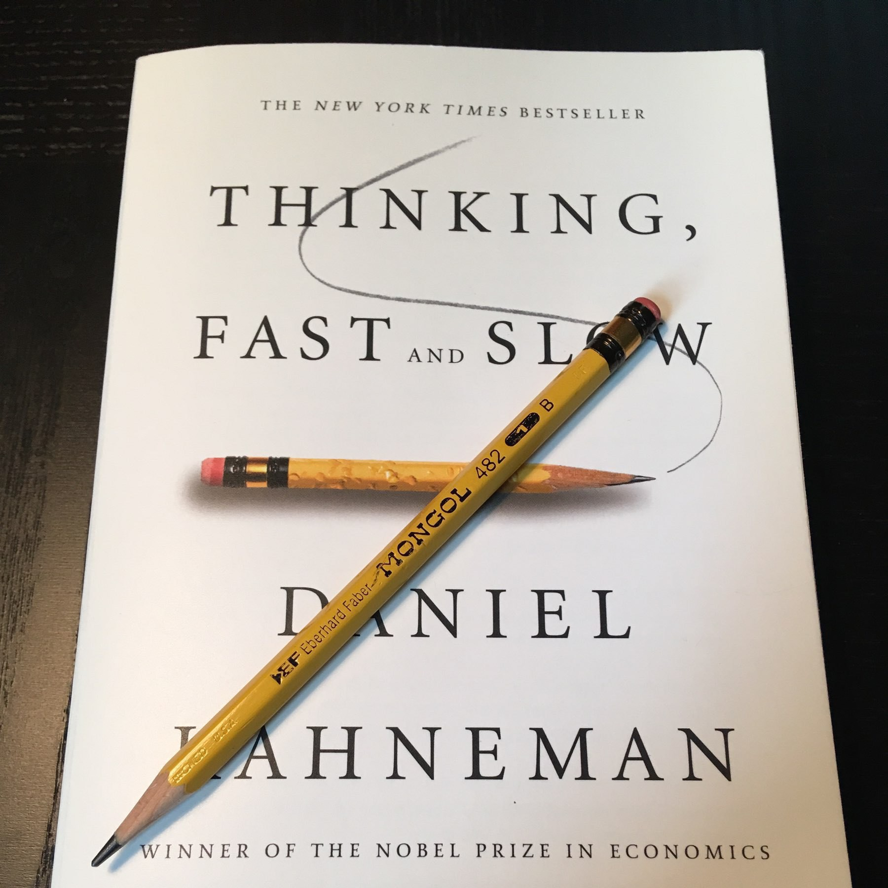 a Mongol pencil resting on the cover of the book Thinking Fast and Slow which features a photo of a Mongol pencil