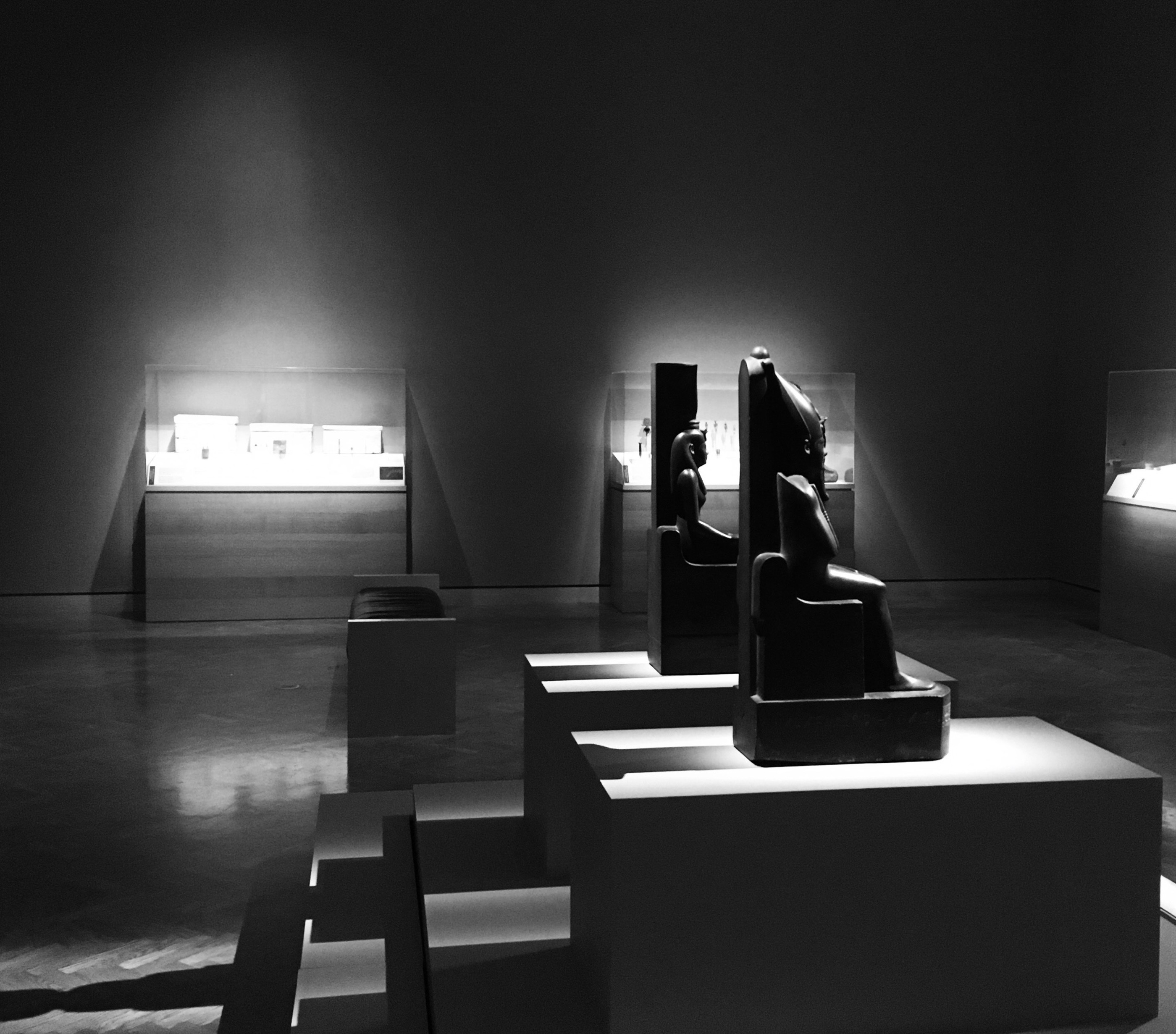 Small statues of Osiris and Isis in a dimly lit gallery with stark lighting