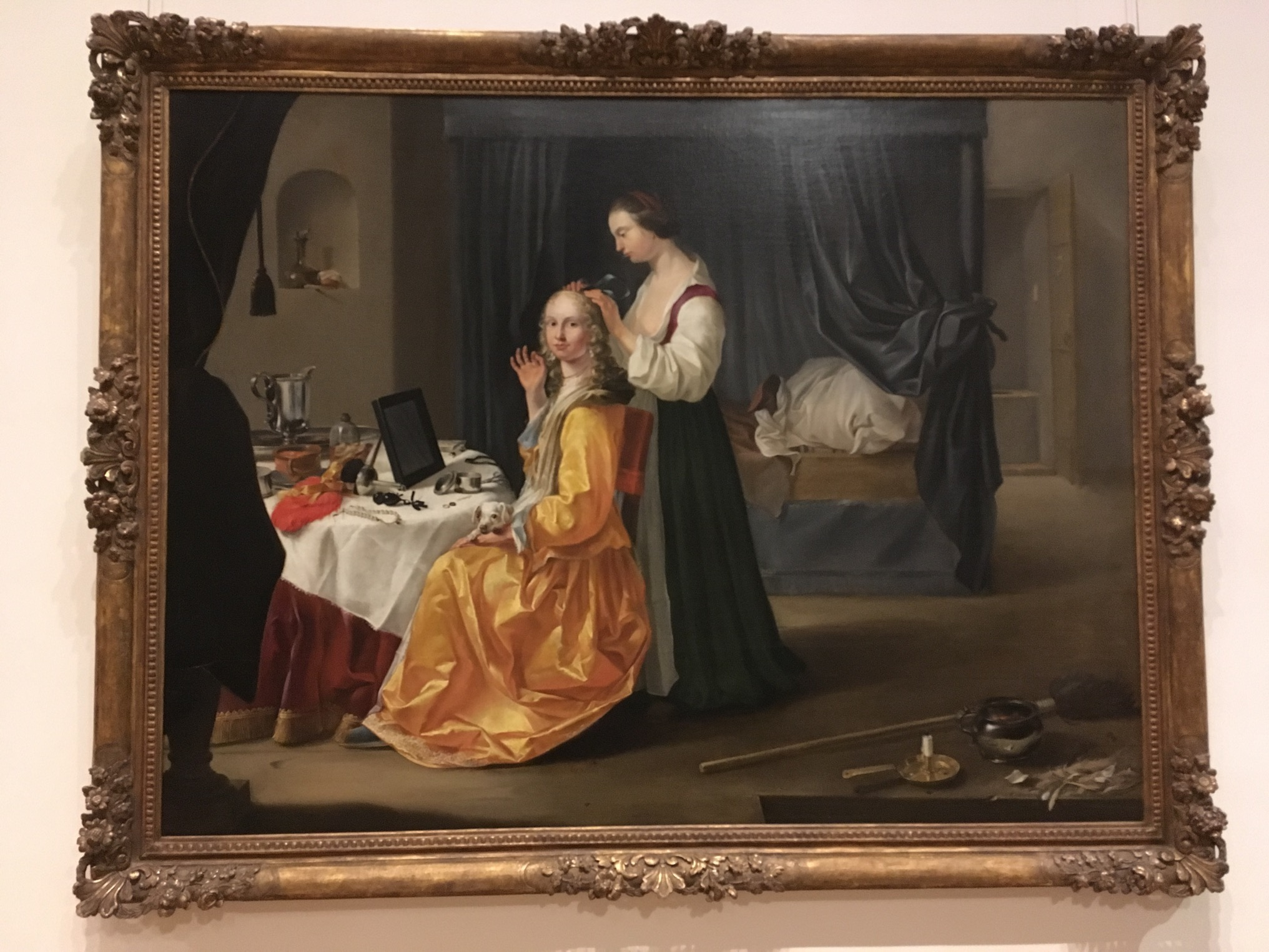 Posh lady at a table in her bedchamber, attended by her handmaiden, with a propped-up slab on the table before her that looks like a small mirror (but which is almost certainly an iPad)