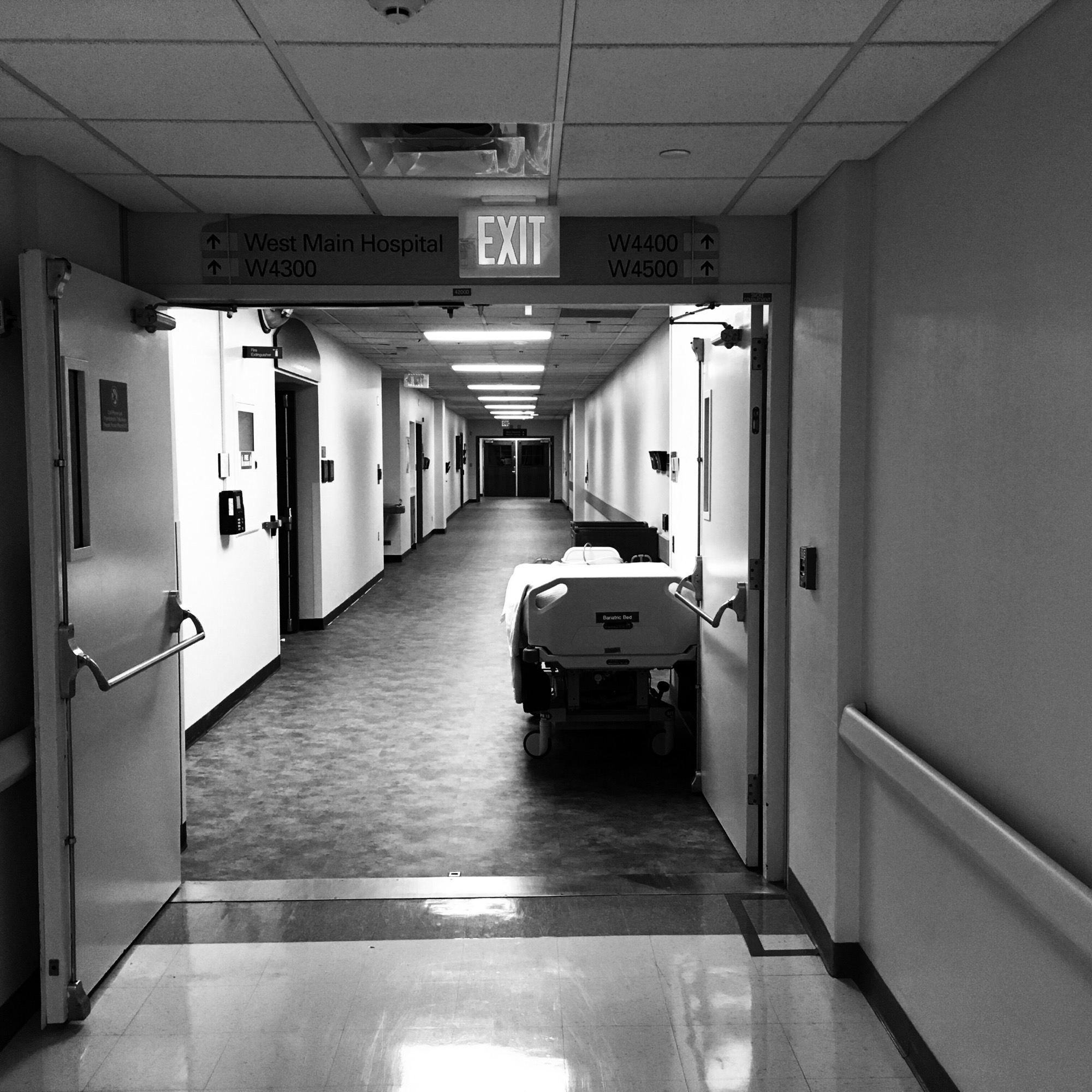 long, empty hospital corridor with empty hospital bed parked in the distance
