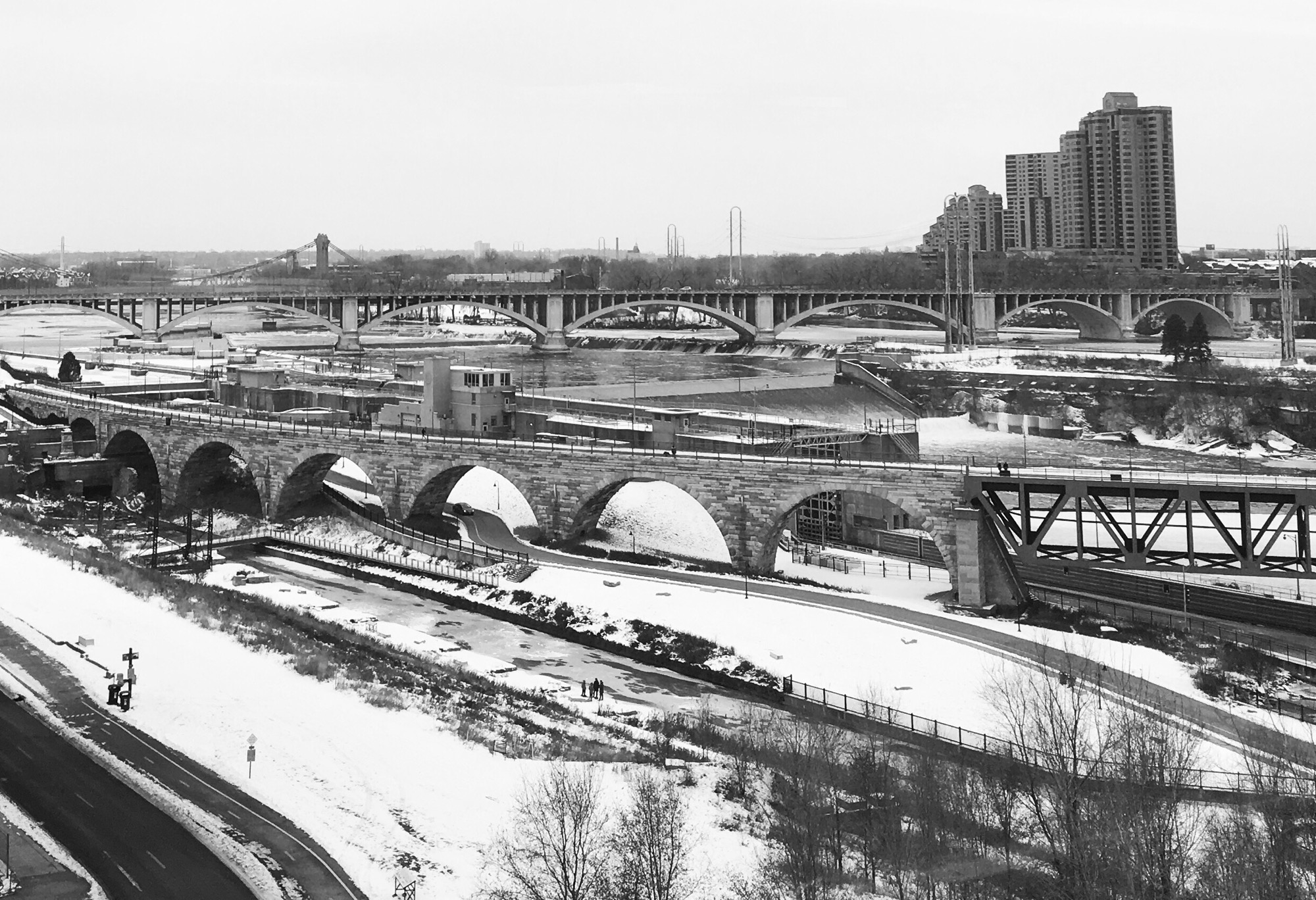 Snow, bridges (Stone Arch, Third Avenue, Hennepin), St Anthony Falls, and the Mississippi River from a high window in the Guthrie Theater