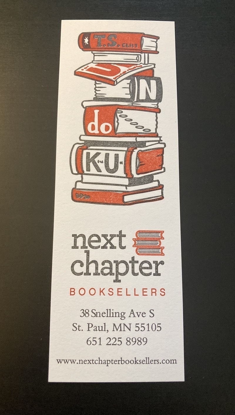 Bookmark with a drawing of a stack of books whose titles spell the word tsundoku