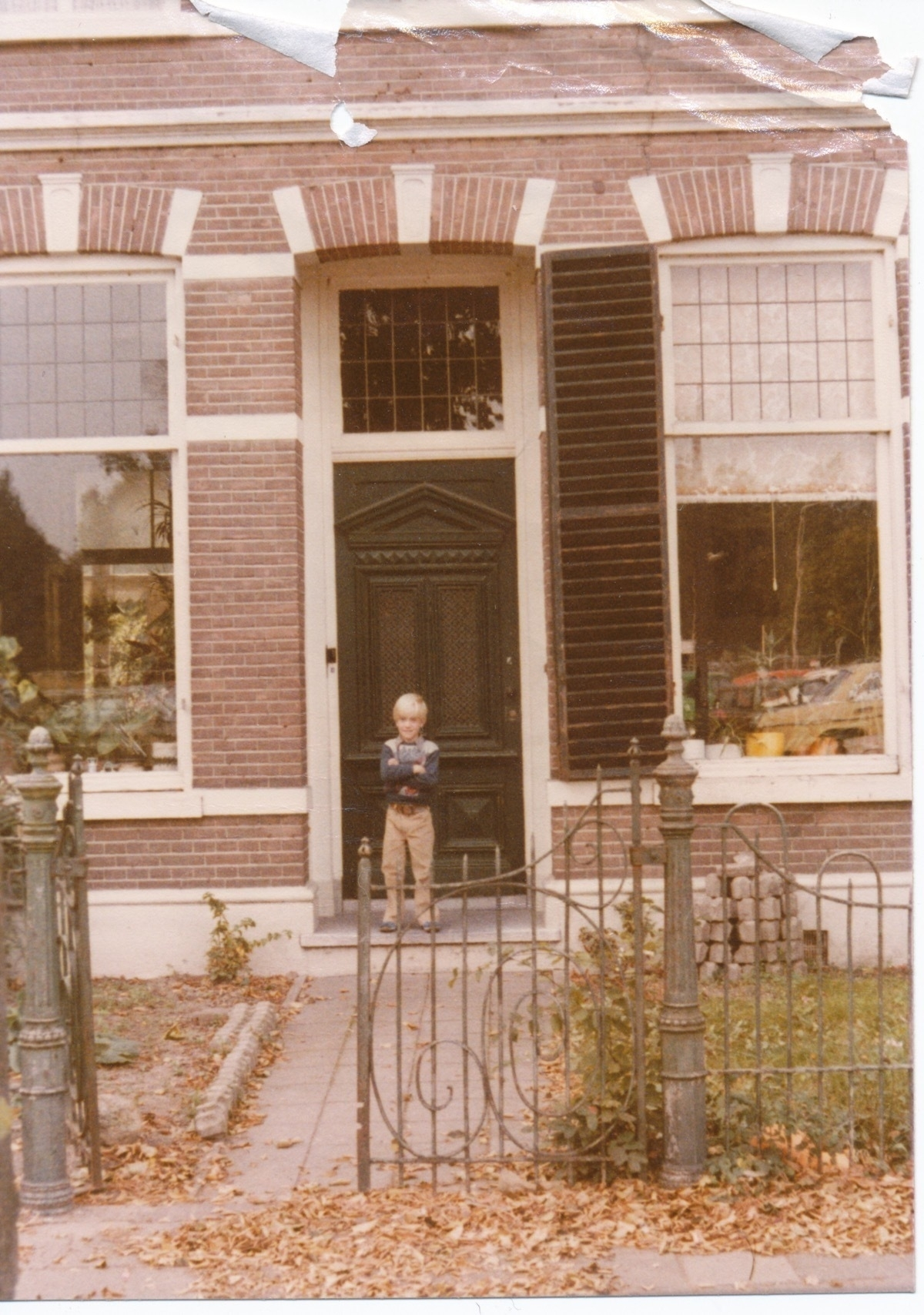 The front of a brick house in the Netherlands in 1977 with me, aged 7, standing at the front door