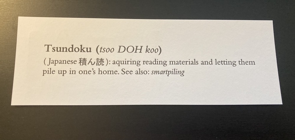 the flipside of the bookmark showing the definition of the word tsundoku: acquiring reading materials and letting them pile up in one's home. See also smartpiling